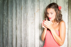Pretty lady with flower in hair smelling cup Royalty Free Stock Photos