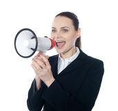 Pretty lady giving instructions with megaphone. Against white background Royalty Free Stock Image