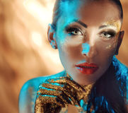 Pretty lady with glossy golden dust on the face. Pretty lady with glittering golden dust on the face Stock Image