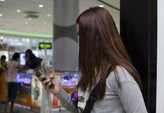 Pretty Lady hairs covers face text messaging with smartphone inside department store. San Pablo City, Laguna, Philippines - December 28, 2016: Pretty Lady hairs royalty free stock photos