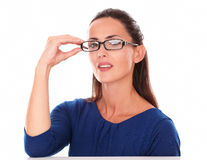 Pretty lady with hand on glasses looking at you Royalty Free Stock Image