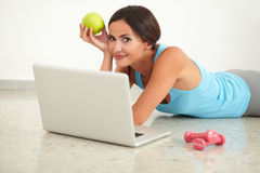 Pretty lady holding apple and working on computer Royalty Free Stock Images