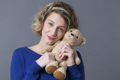 Pretty lady holding cuddly toy remembering childhood Royalty Free Stock Photography