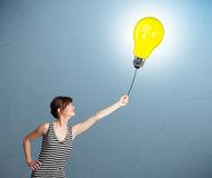 Pretty lady holding a light bulb balloon Royalty Free Stock Photo