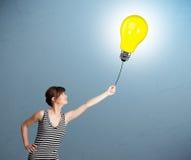 Pretty lady holding a light bulb balloon. Pretty young woman holding a light bulb balloon Royalty Free Stock Photo