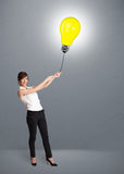 Pretty lady holding a light bulb balloon Stock Images