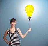 Pretty lady holding a light bulb balloon. Pretty young woman holding a light bulb balloon Stock Images