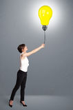 Pretty lady holding a light bulb balloon Stock Photo