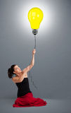 Pretty lady holding a light bulb balloon Stock Image