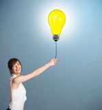 Pretty lady holding a light bulb balloon Royalty Free Stock Image