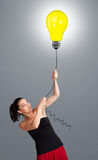 Pretty lady holding a light bulb balloon Royalty Free Stock Images