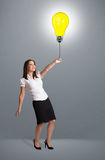 Pretty lady holding a light bulb balloon Stock Photos