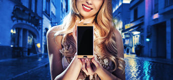 Pretty lady holding a mobile phone. Pretty lady holding a cell phone Royalty Free Stock Photo