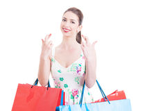 Pretty lady holding shopping bags making crossed fingers gesture Stock Image