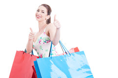Pretty lady holding shopping bags making like approval gesture Royalty Free Stock Photography