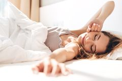 Pretty lady lies in bed indoors. Eyes closed. Image of young smiling pretty lady lies in bed indoors. Eyes closed royalty free stock photo