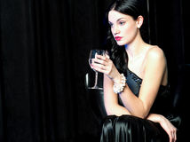 Pretty lady lost in her world, holding wine glass Royalty Free Stock Photos