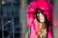 Pretty lady outside in cold weather. Wear jacket with red hood leaning on handrails, horizontal photo royalty free stock photos
