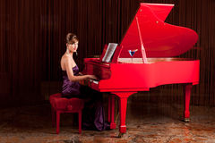 Pretty lady playing the piano Stock Photos
