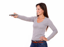 Pretty lady pointing remote control - copyspace Stock Images