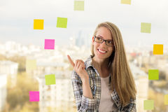 Pretty lady pointing. Pretty smiling lady in glasses standing against window with colorful stickers and pointing at something Stock Photos