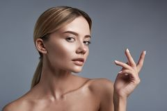Pretty lady putting finders up and looking attentively at you stock image