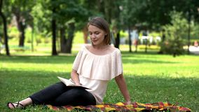 Pretty lady reading romantic novel, sitting on plaid in park, book lover royalty free stock photography