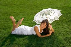 Pretty lady relaxing on the grass. Smiling young pretty girl  in white with umbrella on the lawn Stock Images