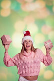 Pretty lady in Santa hat holding two pink gift Royalty Free Stock Images