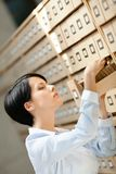 Pretty lady searches something in card catalog Royalty Free Stock Photography