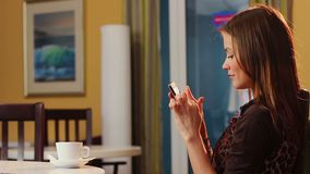 Pretty lady sends phone message sitting in cafe drinking coffee. Stock footage stock footage