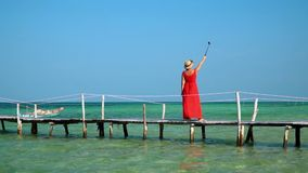 A pretty lady shoots a video of herself with an action camera on a selfie stick. Bright sunny day on the island. Phu. On this video you can see as the woman in a stock video footage