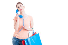 Pretty lady shopper holding telephone receiver as assistance con Royalty Free Stock Photos