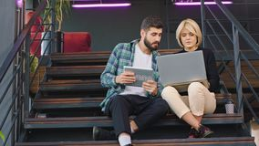 Pretty lady with a short and blonde hair analysing the plan of work with his colleague from office using a notebook