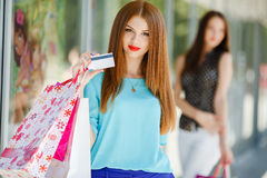 Pretty lady showing credit card in the mall Royalty Free Stock Image