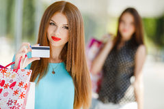 Pretty lady showing credit card in the mall Stock Image