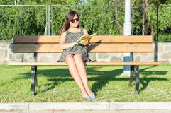Pretty lady sitting on bench and reading Stock Photography