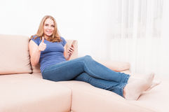 Pretty lady sitting on couch holding smartphone showing like Stock Photography