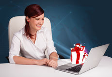 Pretty lady sitting at desk and typing on laptop with present bo Royalty Free Stock Photo
