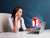 Pretty lady sitting at desk and typing on laptop with present bo Stock Image