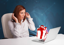Pretty lady sitting at desk and typing on laptop with present bo Stock Photos