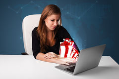 Pretty lady sitting at desk and typing on laptop with present bo Royalty Free Stock Image