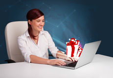 Pretty lady sitting at desk and typing on laptop with present bo Royalty Free Stock Photos