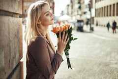 Pretty lady smelling fragrant roses Stock Photos