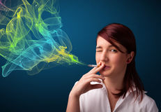 Pretty lady smoking cigarette with colorful smoke Royalty Free Stock Photos