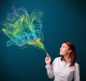 Pretty lady smoking cigarette with colorful smoke Stock Photo