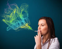 Pretty lady smoking cigarette with colorful smoke Royalty Free Stock Photography
