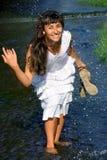 Pretty lady splashing in the stream Stock Image