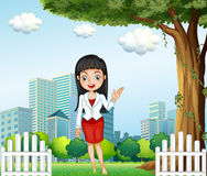 A pretty lady standing near the tree across the buildings Stock Image