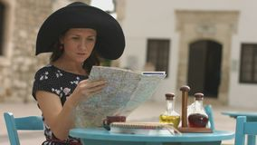 Pretty lady studying city map, searching accommodation, hotel, restaurant, cafe. Stock footage stock footage